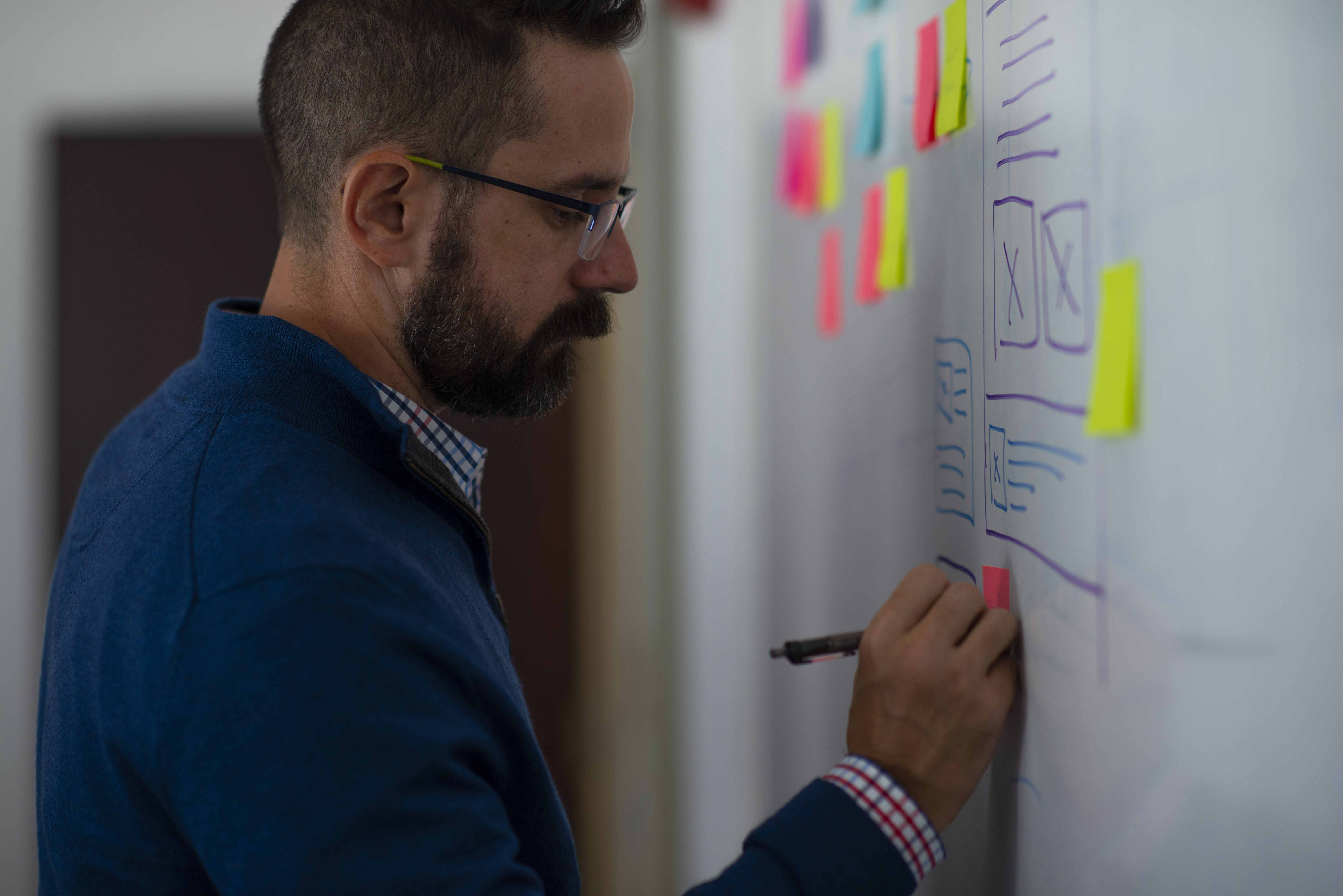 USDP designers Joe (a man with dark hair, beard, and glasses), strategizing on a whiteboard in a conference room.