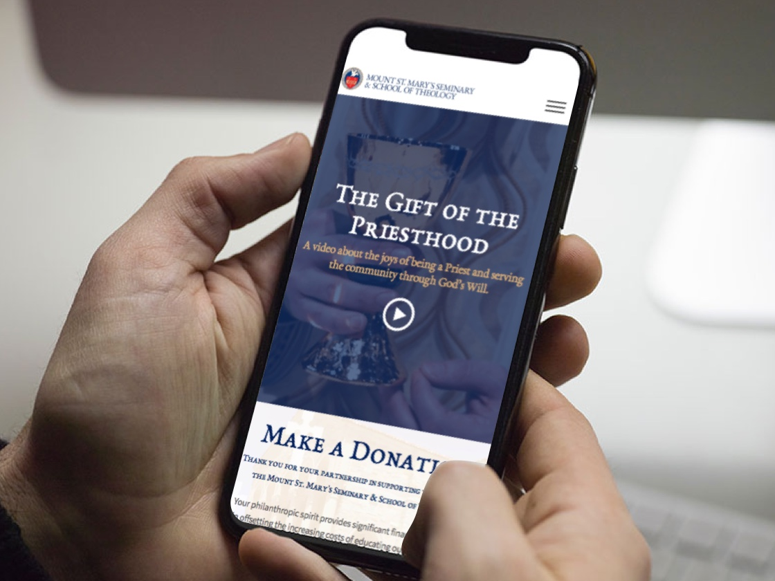 Image of a person holding an iPhone with the Mount St. Mary's homepage on the screen.