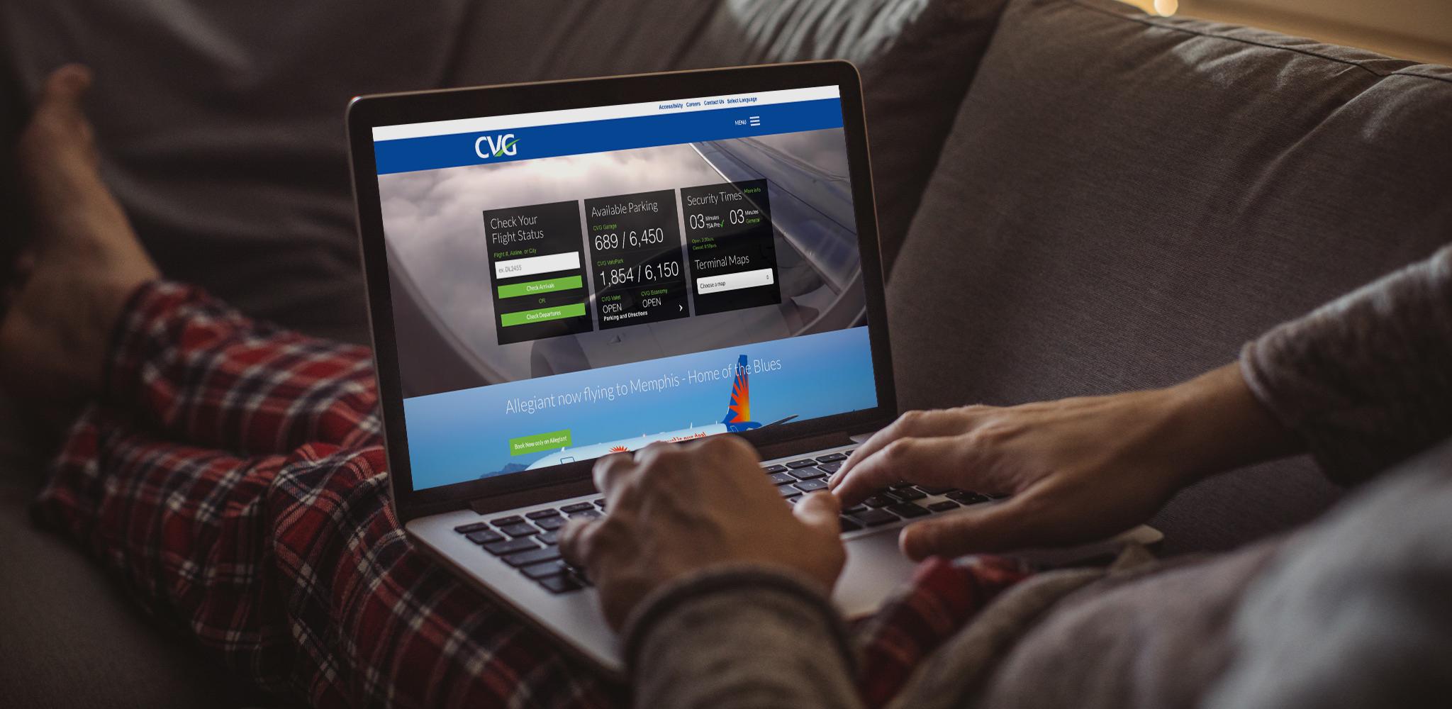 Man sitting on sofa browsing website on his laptop.