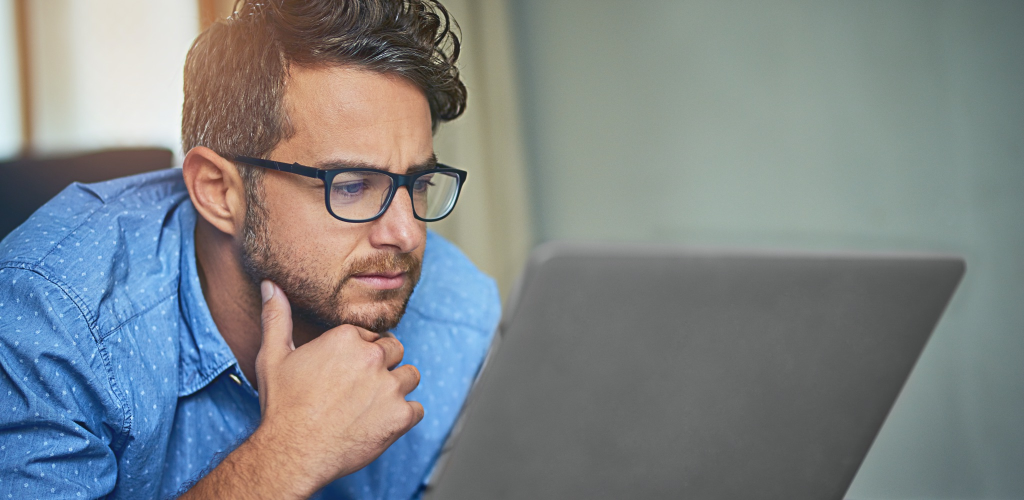 Man in a blue shirt and glasses looking at laptop screen.