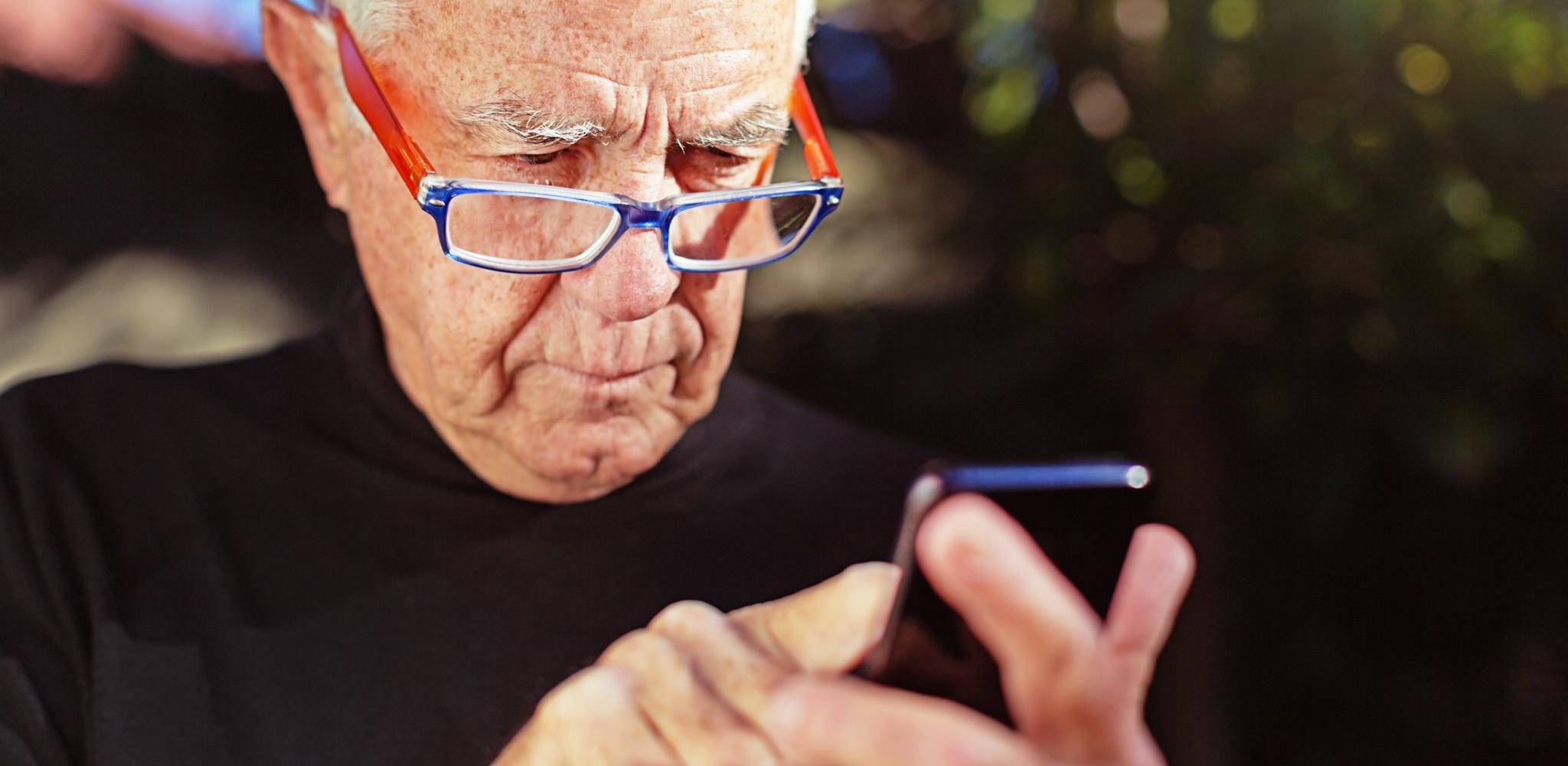 Senior man squinting over rim of glasses at phone.
